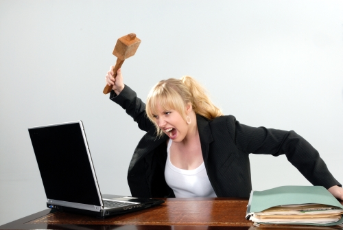 angry businesswoman hits computer with mallet