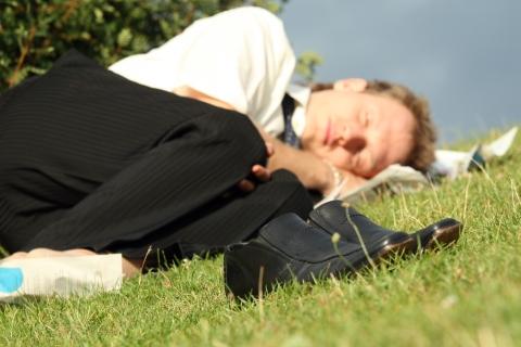 businessman sleeping in park