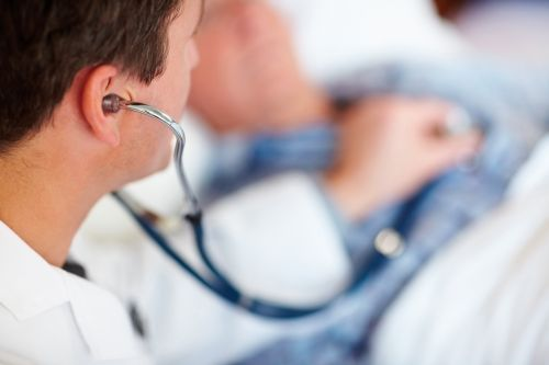 Doctor examining a patient's heart beat with a stethoscope
