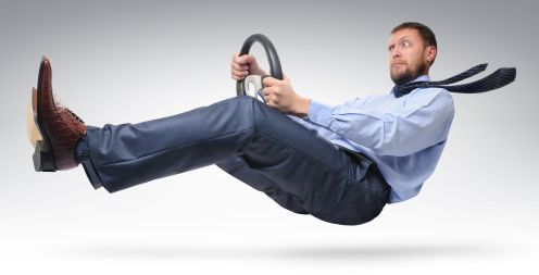 Businessman driver in a tie with a wheel