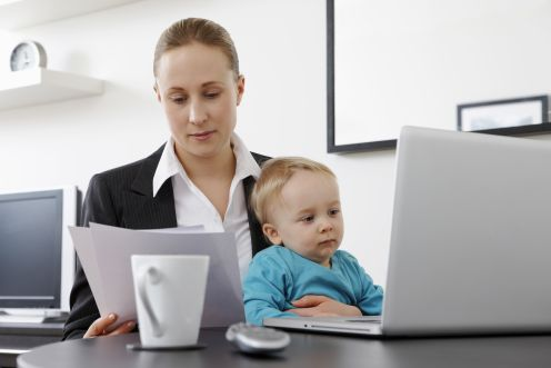 Businesswoman working from home holding her baby son