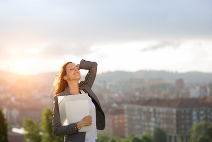 Young female entrepreneur enjoying business success against city and sunset background. Successful businesswoman smiling outdoor.