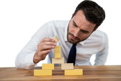Businessman placing wooden block on a tower