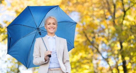 businesswoman with umbrella over autumn background